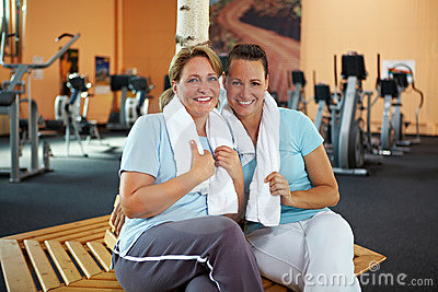 Happy women sitting in gym