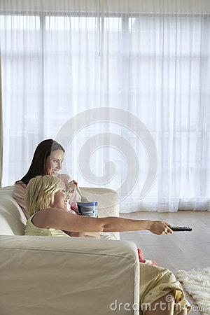 Happy Women Watching TV On Sofa