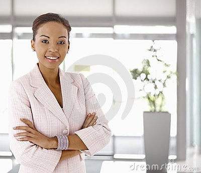 Happy young afro-american woman in office lobby