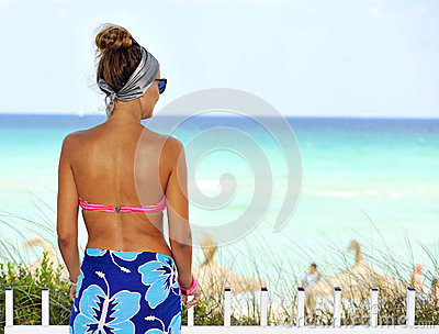 Happy young attractive woman in pink bikini posing at paradise beach