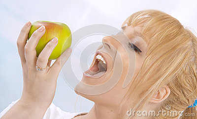 Happy young blond woman with an apple