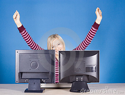 Happy young blonde woman at the two computer s screens