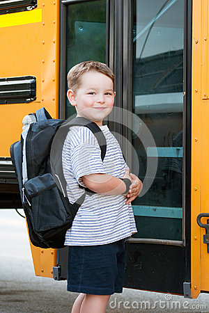 Happy young boy in front of school bus