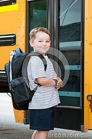 Happy young boy in front of school bus