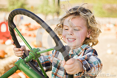 Happy Young Boy Playing on an Old Tractor Outside