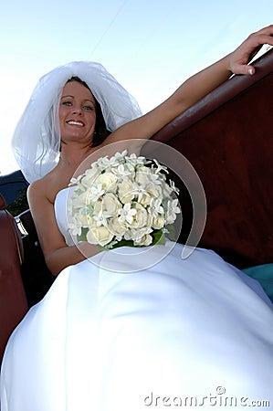 Happy young bride in convertible