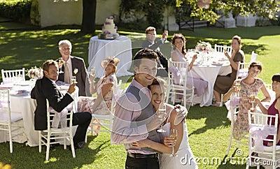 Happy Young Bride And Groom Embracing In Garden