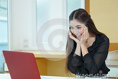 Happy young business woman looking at laptop screen surprised