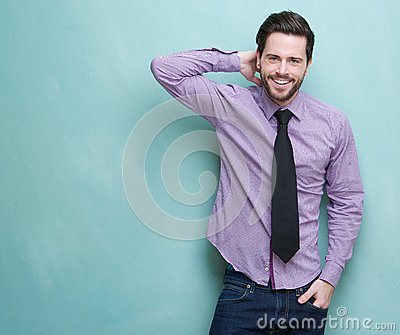 Happy young businessman smiling against blue background Stock Photo