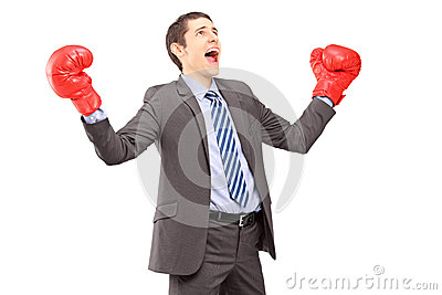Happy young businessman in suit with red boxing gloves gesturing