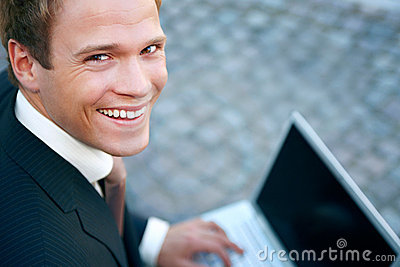 Happy young businessman using laptop on street