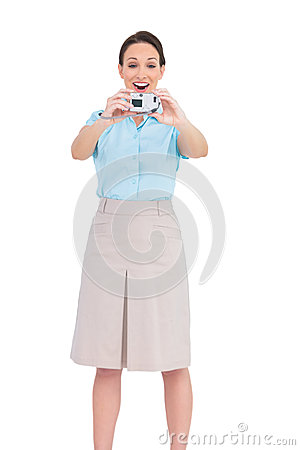 Happy young businesswoman taking picture of herself