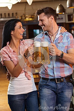 Happy young couple clinking with beer in pub