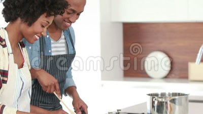 Happy young couple cooking together. In the kitchen