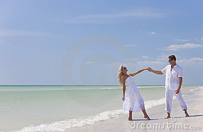 Happy Young Couple Dancing Holding Hands on Beach