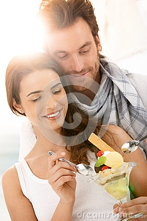 Happy young couple eating icecream on summer beach