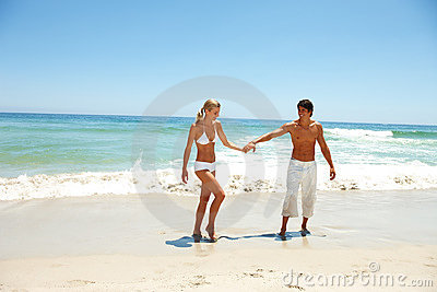 Happy young couple enjoying together on beach