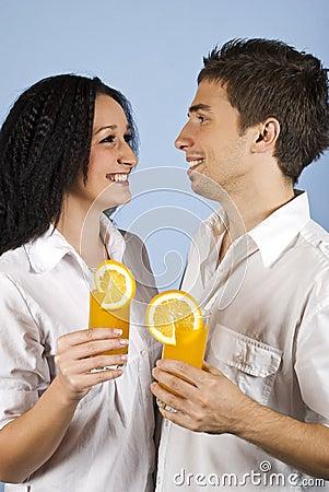 Happy young couple with fresh orange juice
