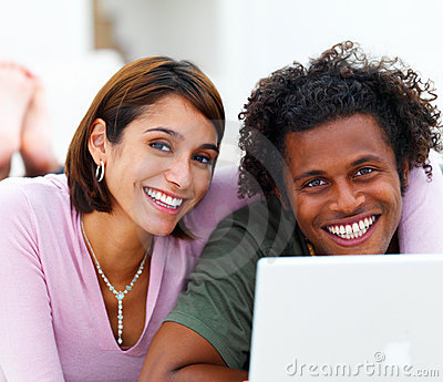 Happy young couple in front of a laptop