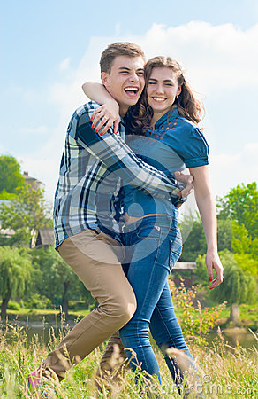 Happy Young couple in fun hugging & blue sky