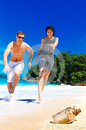 Happy young couple having fun on the shore of a tropical for Tropical vacations for couples