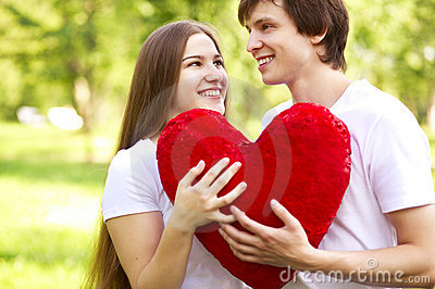 Happy young couple holding big red heart
