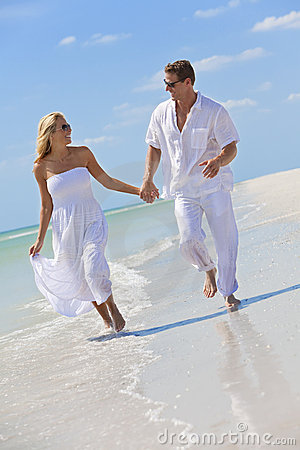 Happy Young Couple Holding Hands on A Beach