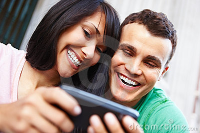 Happy young couple looking at cell phone