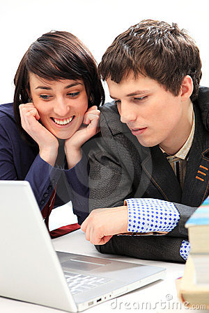 Happy young couple looking at laptop.