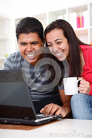 Happy young couple looking at a laptop
