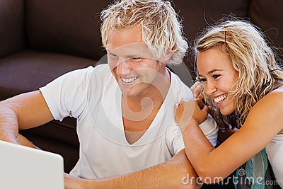 Happy young couple looking at laptop