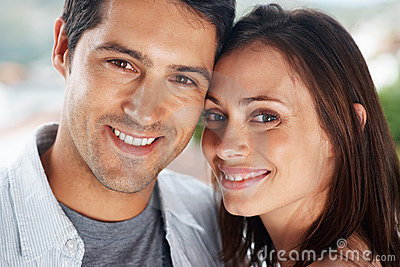 Happy young couple looking at you with a smile