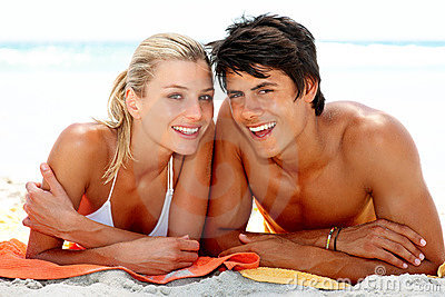 Happy young couple lying down at the beach togethe