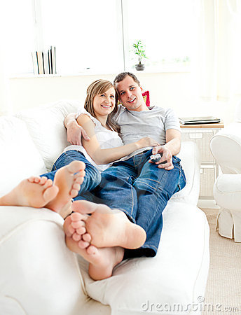 Happy young couple lying together on the couch