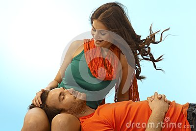 Happy young couple with man in lap of girlfriend