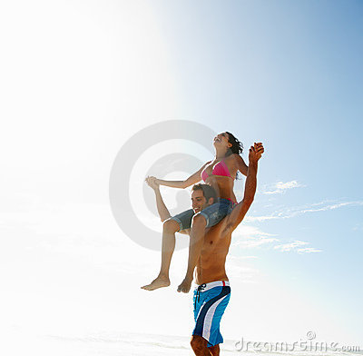 Happy young couple in a playful mood by the beach
