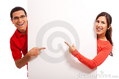 Happy young couple pointing to copy space