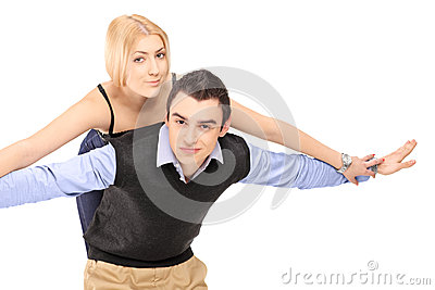 Happy young couple posing piggyback
