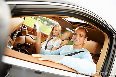 Happy young couple seated in their new car