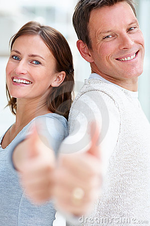 Happy young couple showing thumbs up sign