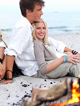 Happy young couple sitting by bonfire at beach in
