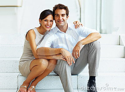 Happy young couple sitting on stairs of a building