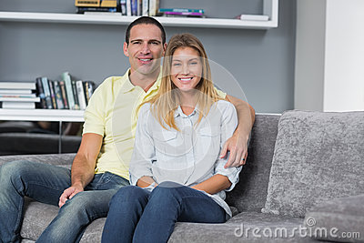 Happy young couple sitting on their couch