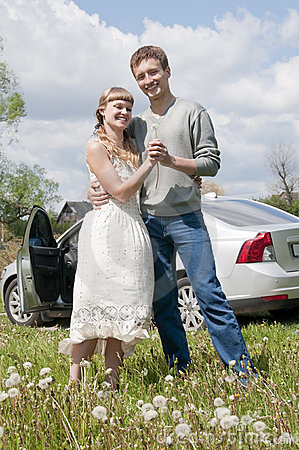 Happy young couple standing near the car