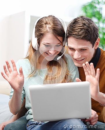 Happy young couple talking through the computer with video chat
