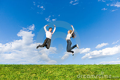 Happy Young Couple - team is jumping in the sky