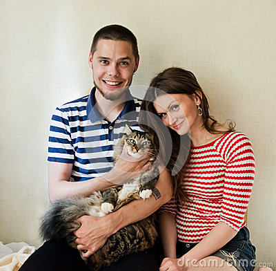 Happy young couple with their cat