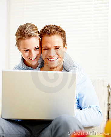 Happy young  couple using laptop in the house