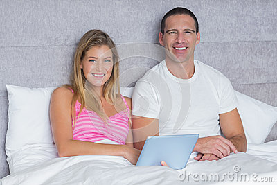 Happy young couple using their tablet pc together in bed