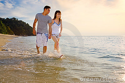 Happy young couple walking along the beach